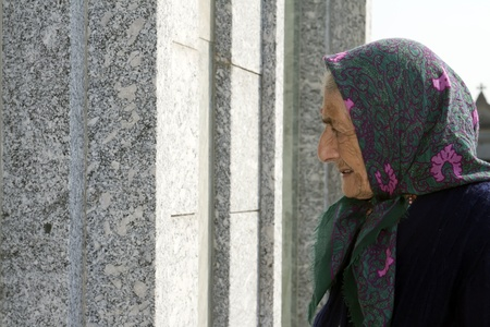 senior woman loks at a tomb in a cemetery
