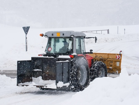 snowplow tractor cleaning a road in winter time photo
