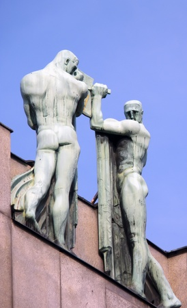 nudes: bronze male nude statues at the top fo a building in Prague Stock Photo