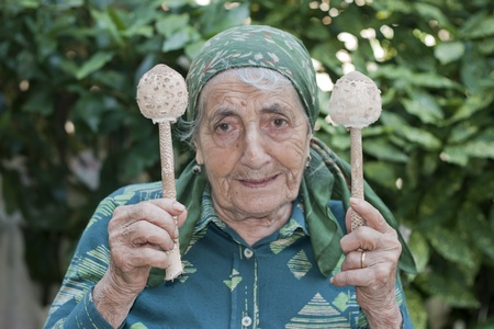senior woman shows two mushrooms photo
