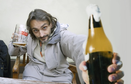 man holding a bottle and a glass of beer photo