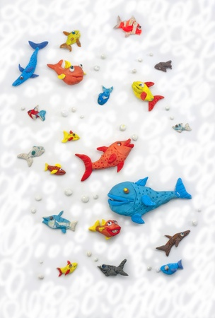 colorful plasticine fishes swimming on light background