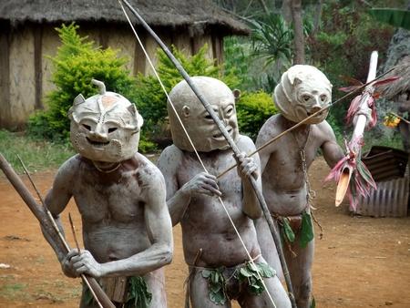 PAPUA, NEW GUINEA - SEPTEMBER 16: Mudmen warriors clasp their weapons at Goroka Tribal Festival. Papua New Guinea on September 16, 2011 Editöryel