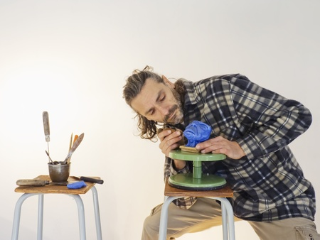 sculptor: sculptor at work on an alien head miniature Stock Photo
