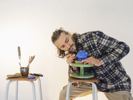 sculpting: sculptor at work on an alien head miniature Stock Photo