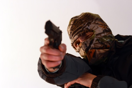 terrorist with ski mask shooting with a pistol photo