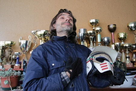 motorcyclist pose with helmet over a victory cup background photo