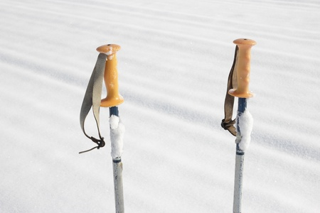 close up of an old pair of ski poles in the snow photo