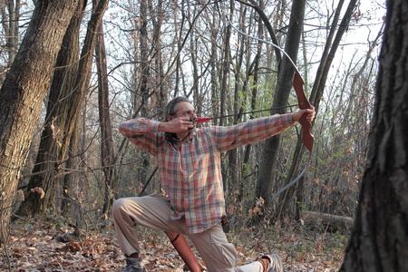man drawing a recurve Bow in the forest photo