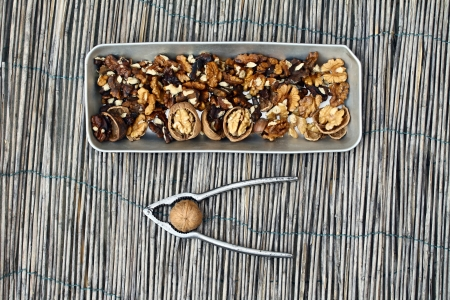 Cracking walnuts with nutcracker on a natural background photo
