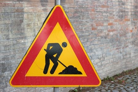 men at work, traffic sign on a brick wall photo