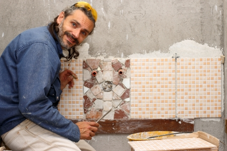 Tiler working on a mosaic in a bathroom photo