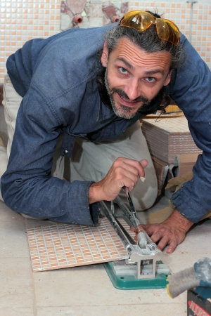smiling tile worker cutting tiles in a bathroom Stock Photo - 13905937