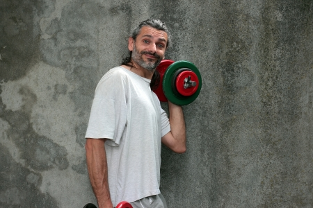 smiling man lifting dumbbell over a grunge background photo