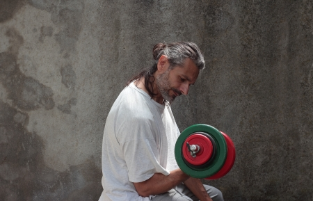 mature man lifting dumbbell over a grunge background photo