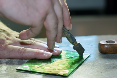 close up hands cutting glass for stained glass Stock Photo