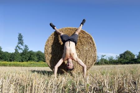 cabeza abajo: hombre al revés feliz en campo de verano Foto de archivo