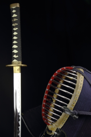 katana sword and kendo helmet over black background photo