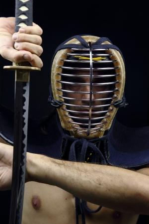 swordsmanship: man holding samurai sword in dramatic studio light