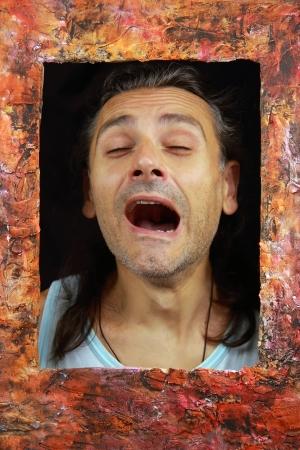 boring frame: man yawning behind a picture frame
