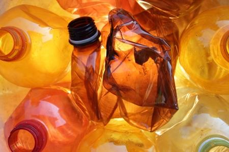 several orange empty crushed plastic bottles
