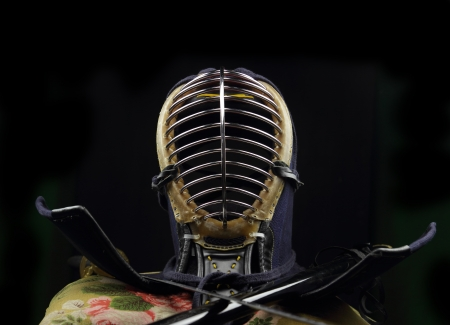 Kendo Helmet and Katana sword over black background