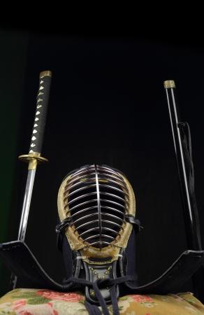 swordsmanship: Kendo Helmet and Katana sword over black background