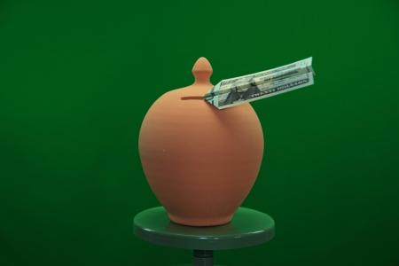 dollar bill flying in a money box