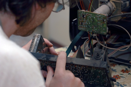 close up of a  Man repairing an old television photo