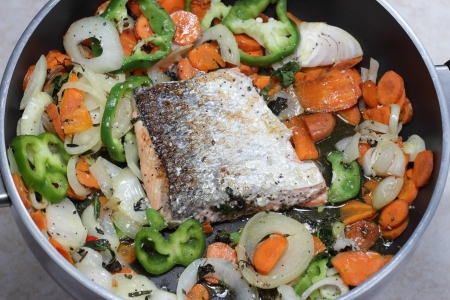 Cooking Salmon fillet in the pan with vegetables