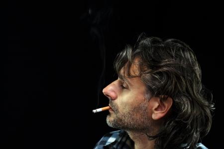 profile of a man smoking cigarette over black Stock Photo