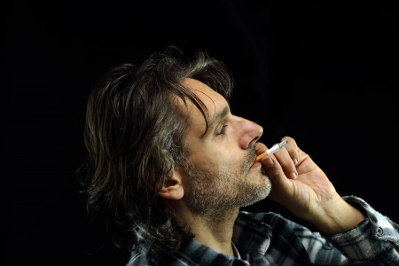 profile of a man smoking cigarette over black photo
