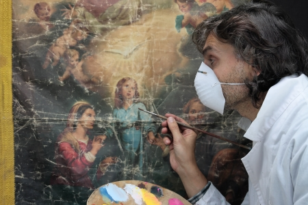 restorer at work on damaged ancient painting Stock Photo