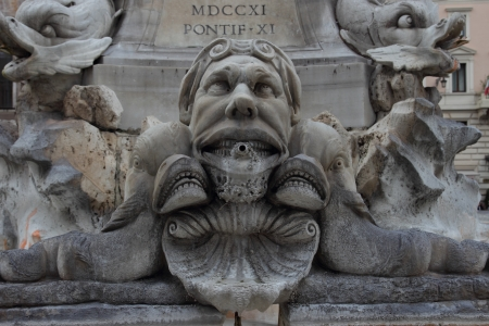gruesome: Grotesque mask on the fountain of Piazza della Rotonda in fron of the Pantheon in Rome Italy Stock Photo
