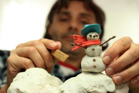 out of focus: out of focus puppet maker working on a snowman Stock Photo