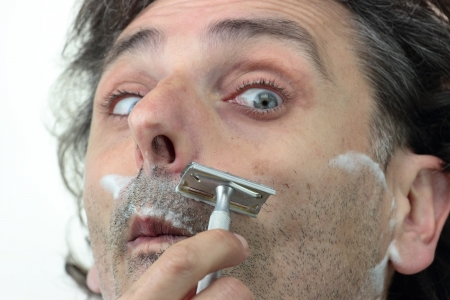a man shaving with an old style razor photo