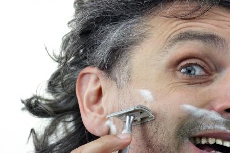 Man shaving his cheek using vintage razor photo