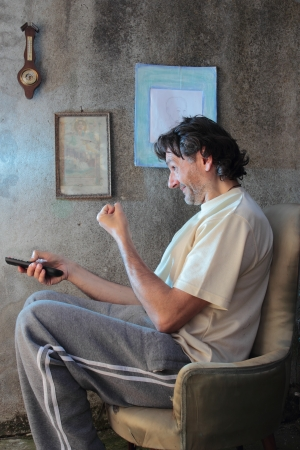 exultant: exultant man with remote control sitting on armchair
