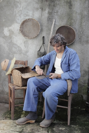 machete: man in a retro interior sharpening a machete Stock Photo