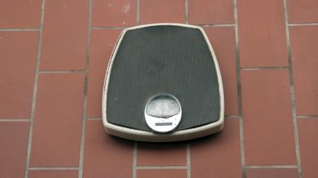 Retro bathroom scales on ceramic tiles floor Stock Photo