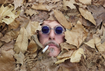 man smoking a joint under a bed of falling leaves photo