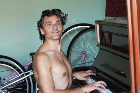 informal: male shirtless pianist looking at camera in informal interior