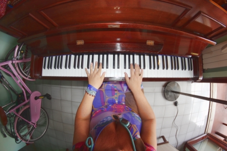 fish-eye view of a woman playing piano at home photo