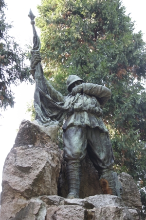 a memorial to fallen soldiers: NOVARA, ITALY - SEPTEMBER 26   First World War memorial, Italian soldier bronze statue in San Nazzaro della Costa park on September 26, 2013 in Novara, Italy  Artwork by Giuseppe Enrini