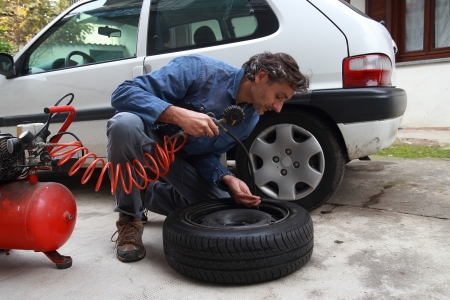 air pressure: caucasian mechanic inspecting the tire pressure Stock Photo