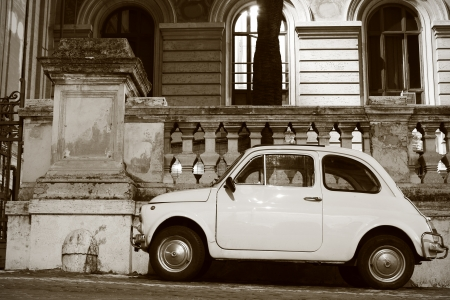 vintage car fiat 500 parking in front of a classic old roman building