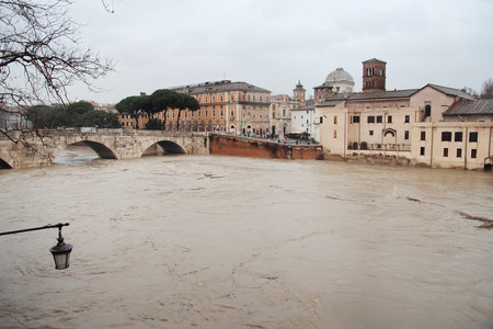 swamped: ROME, ITALY - JANUARY  13, 2014:  The rising level of the River Tiber near Isola Tiberina , central Italy is swamped by torrential rain.   Editorial