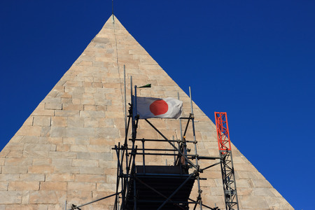 Japanese Flag on Piramide Cestia in Rome, Italy.The restoration is sponsored by a Japanese businessman