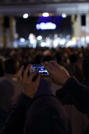 martiri: NOVARA, ITALY - MAY 14, 2014: Man takes Photos at the European election rally during the Beppe Grillo speaking in Martiri square