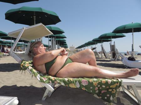 middle age woman sun bathing in bikini Stock Photo